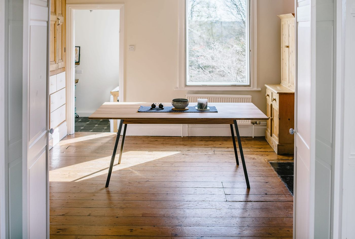 Bespoke dining table designed and manufactured by From Works of steamed beech timber table top and compound angle mild steel legs.