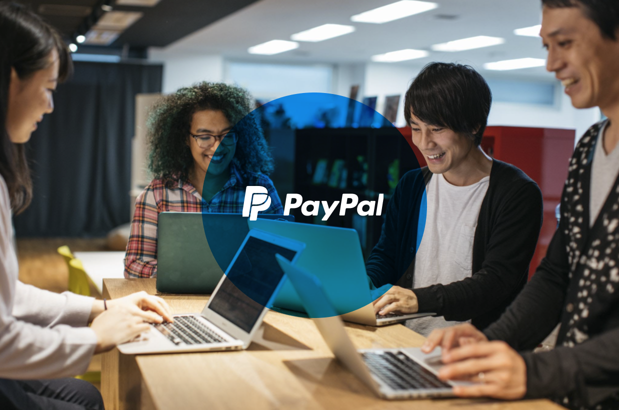 banner with coworkers around table, smiling, with PayPal logo