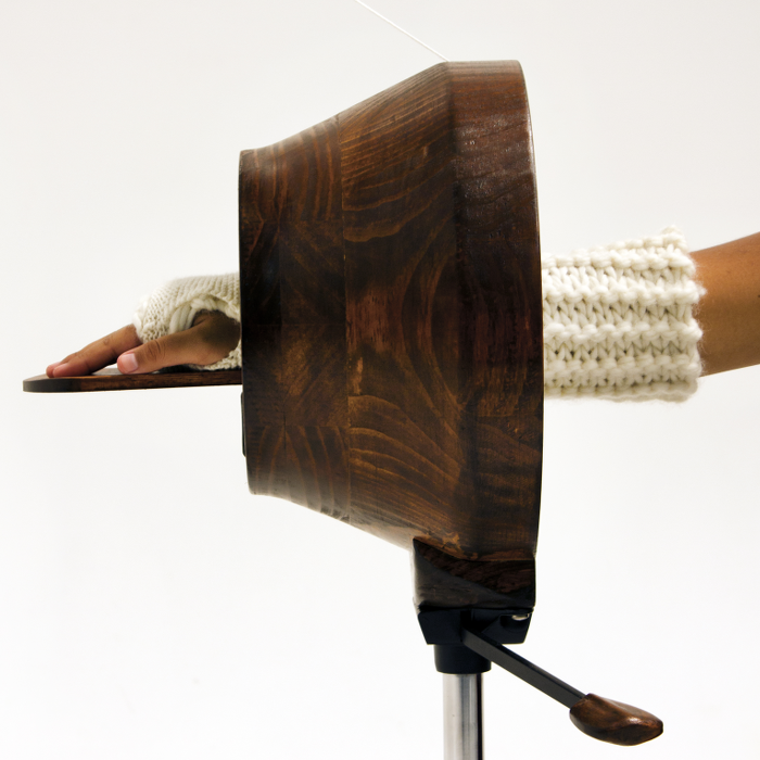 a round, hollow wooden hand-cranked knitting machine creates a wool cast for a human arm at the limb passes through it.