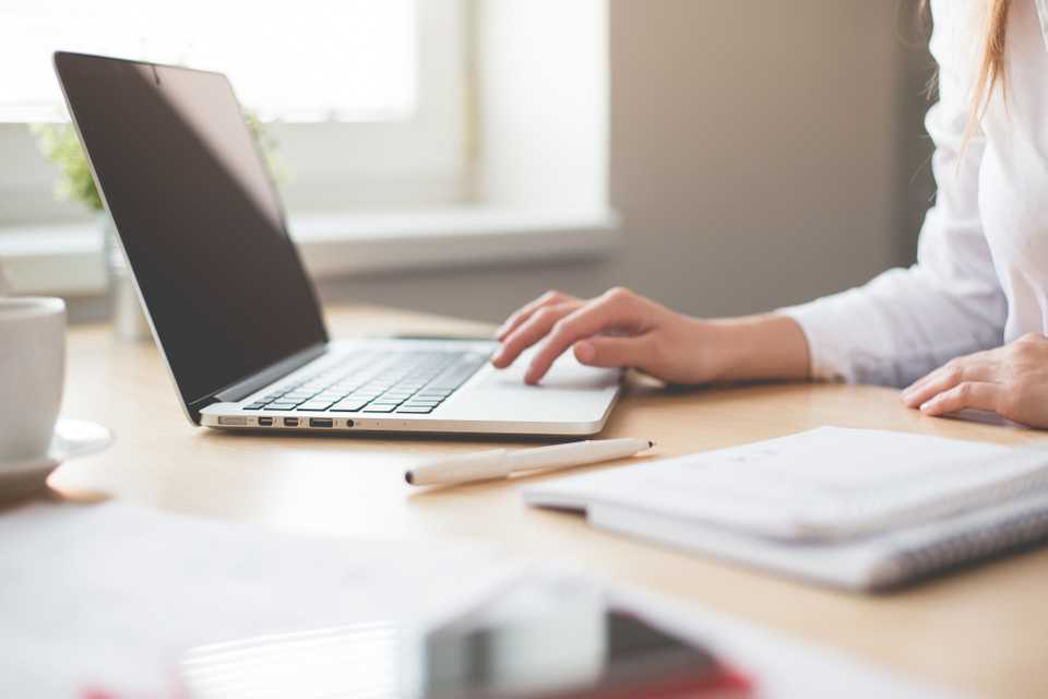 Business worker or entrepreneur working in office on a laptop with a pen and pad