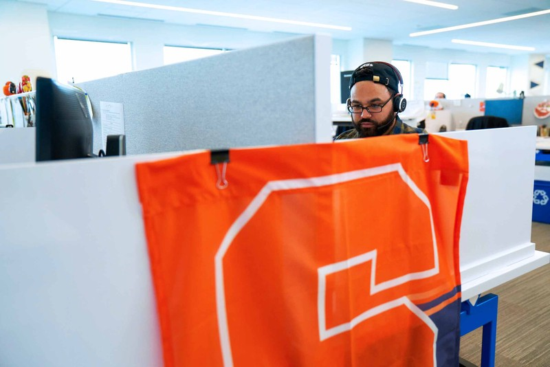Man with headphones on next to a Syracuse University banner draped over the side of his cubicle