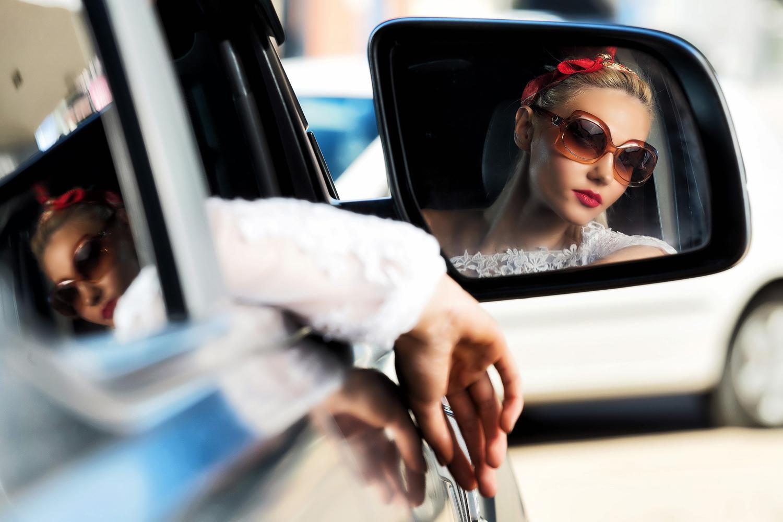 Reflection of women in car side mirror