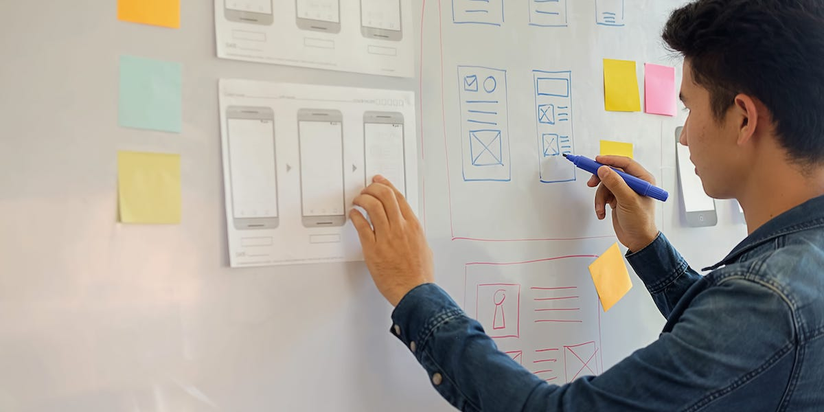 A designer transferring his paper wireframes onto a whiteboard