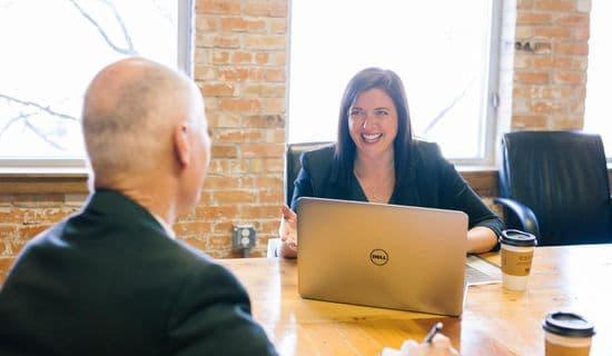 Frau vor Laptop mit Mann an Tisch