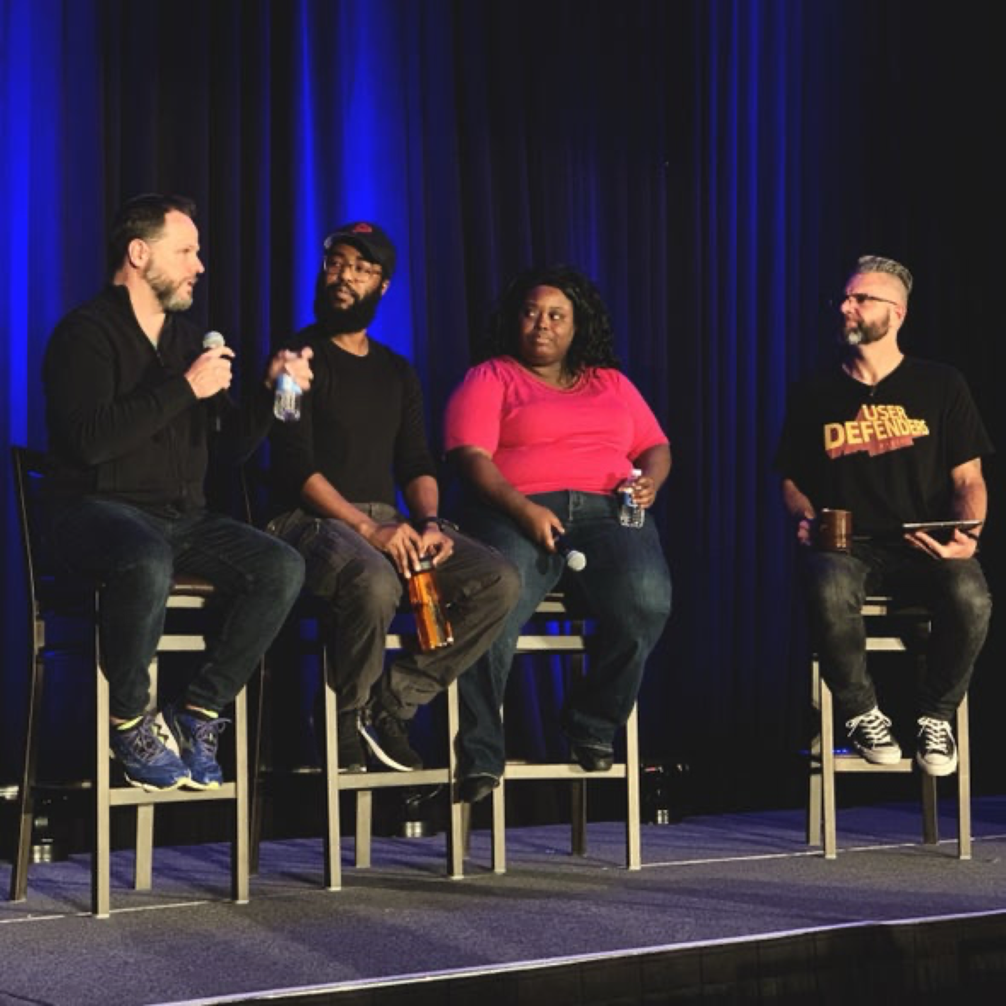 User Defenders Podcast live on stage at An Event Apart Denver. From Left to right, Derek Featherstone, Farai Madzima, Mina Markham and Jason Ogle sitting on stage on stools with a blue curtain backdrop. Photo courtesy of Jeffrey Zeldman