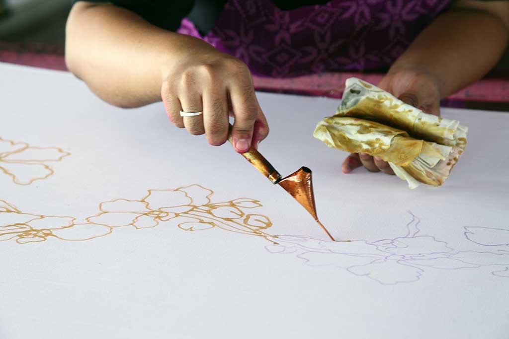 An artist carefully traces the floral motif on a traditional batik fabric using melted wax