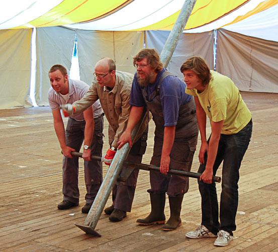 Opbouw van tent: vier mensen zetten tentpaal recht