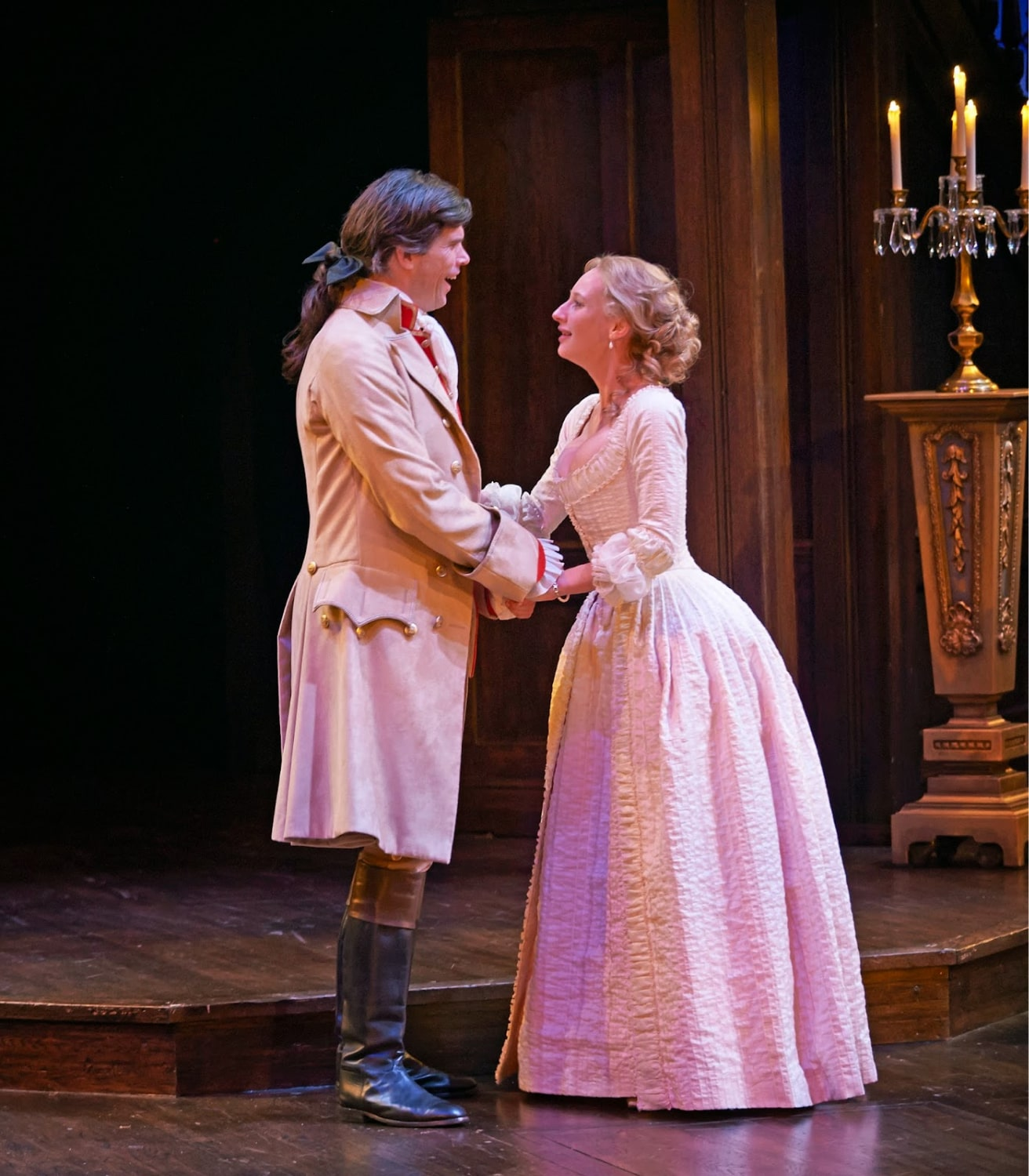 Man in boots and long coat holds hands with woman in white gown.