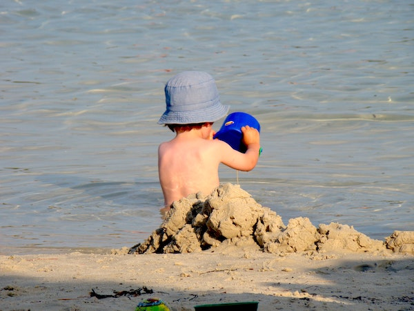 niño en la playa con gorro