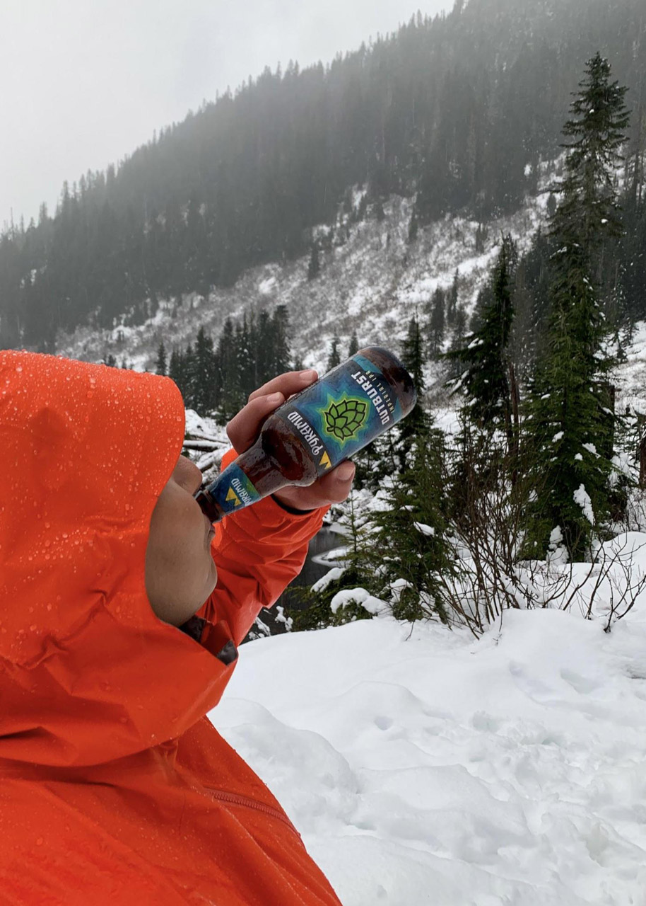 Joanna Genovese wearing an orange raincoat and drinking from a bottle of Pyramid Outburst Imperial IPA. In the brackground is a snow covered forest on a mountainside.