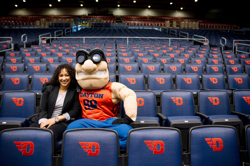 University of Dayton's mascot, Rudy Flyer, poses for a seated photo with a student in UD Arena