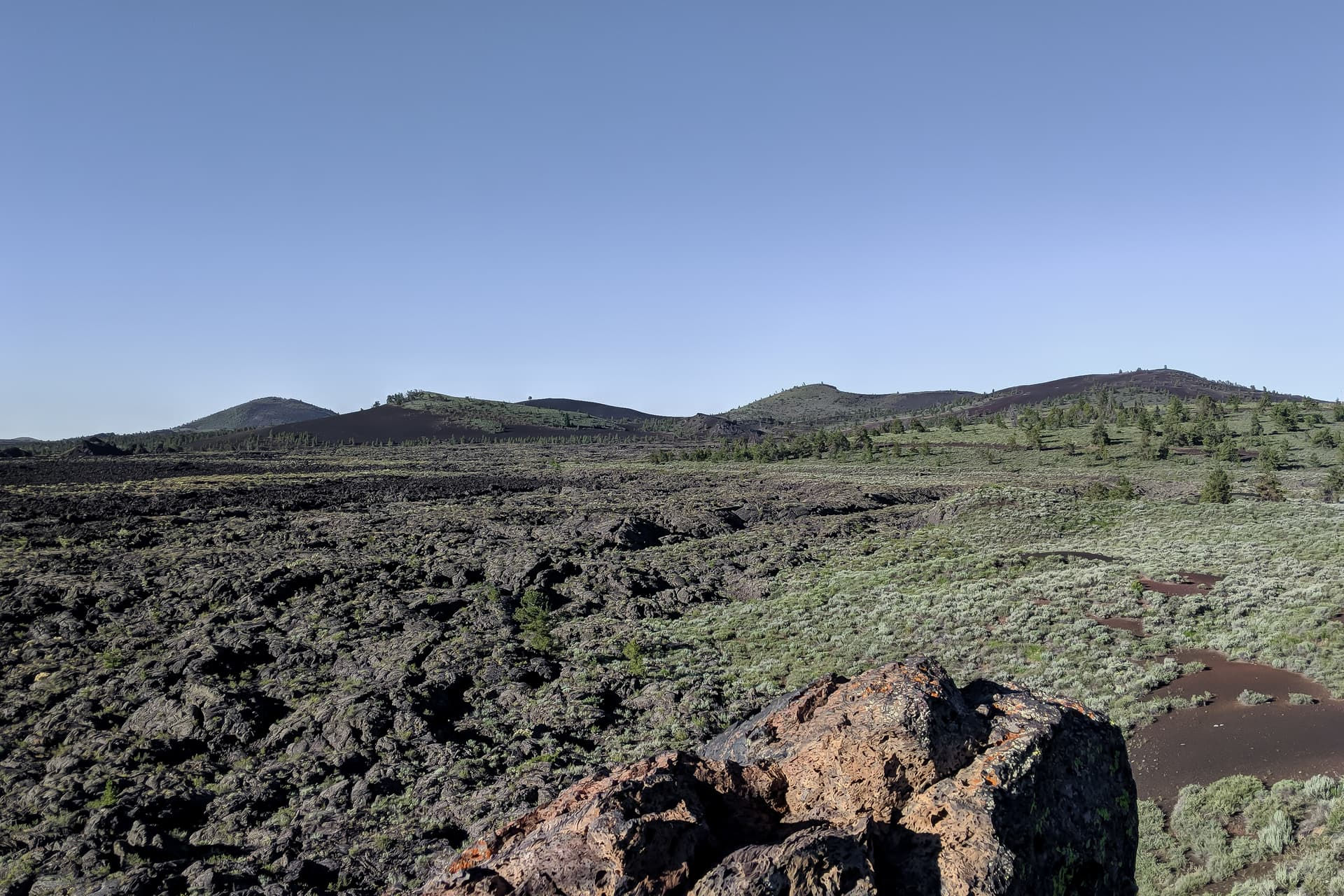 Desert scrubland abruptly ends in a dark, jagged lava field. Beyond, low cinder cones.