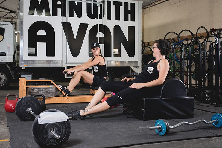 Two women in Man With A Van uniform work out on the company gym equipment.