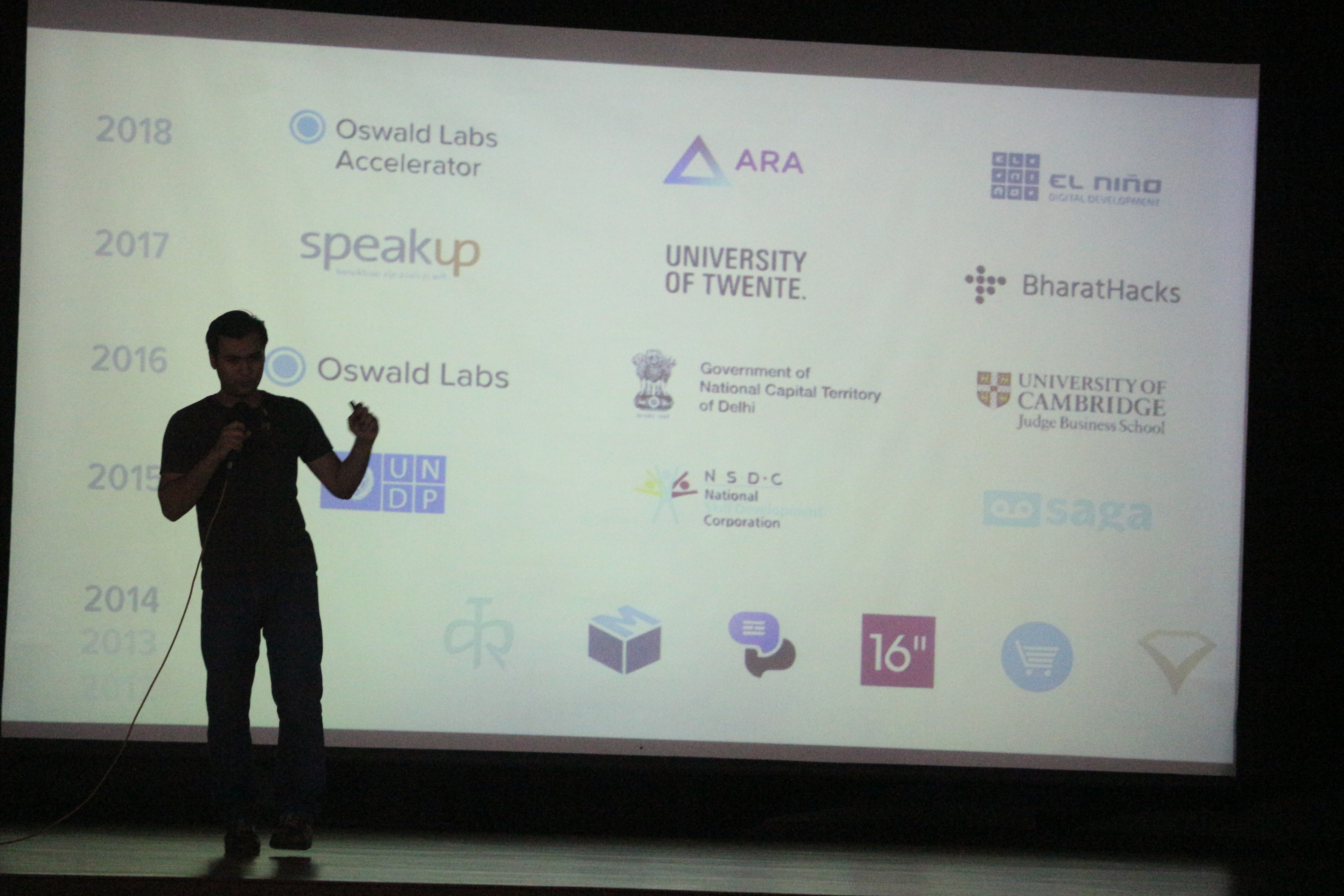 Anand Chowdhary speaking behind a set of logos