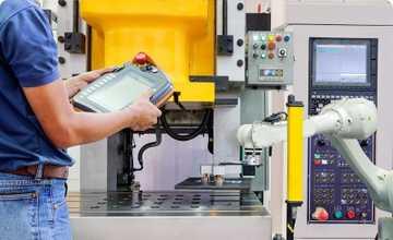 Industrie du futur 4.0 - dans un environnement industriel , une personne de dos, tient une tablette présentant des informations . On suppose qu'elle assure le pilotage d'un robot blanc situé en arrière plan sur la photo. Le site industriel parait très propre et moderne.