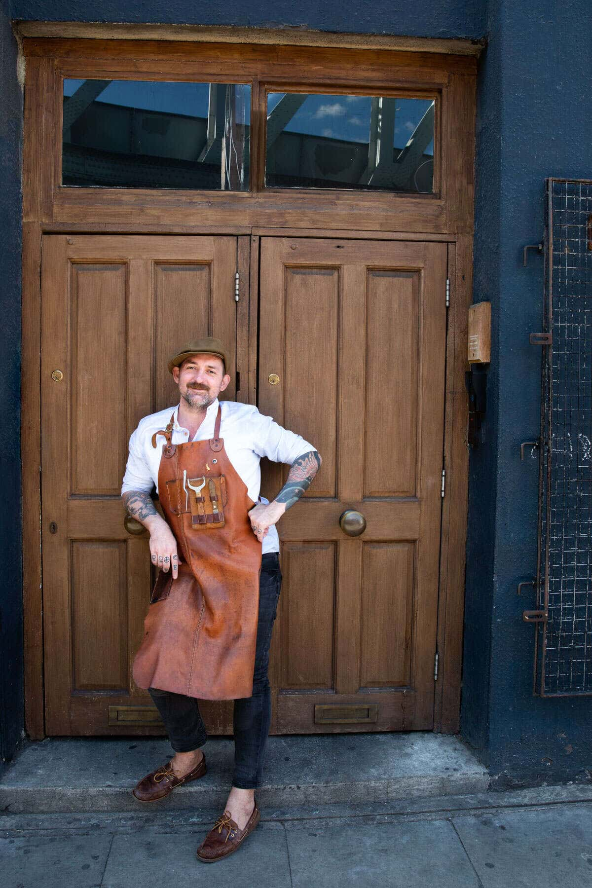 A portrait of a bartender in his apron stood in front of some large wooden doors.