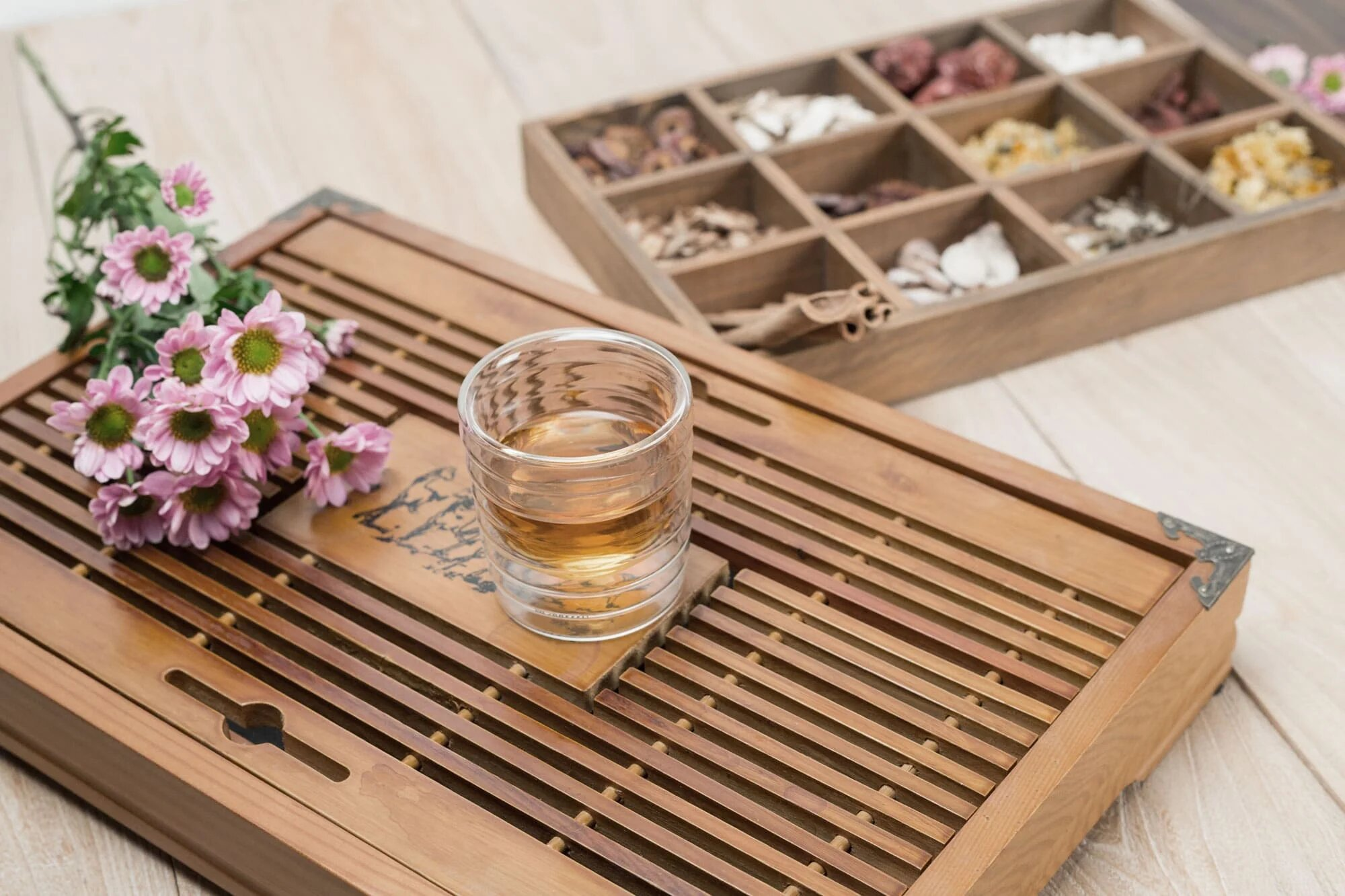 Wooden tray with glass of tea and pink flowers placed on top