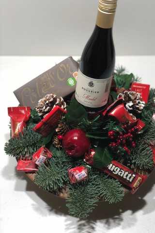 Rond rood kerststuk met fles rode wijn
