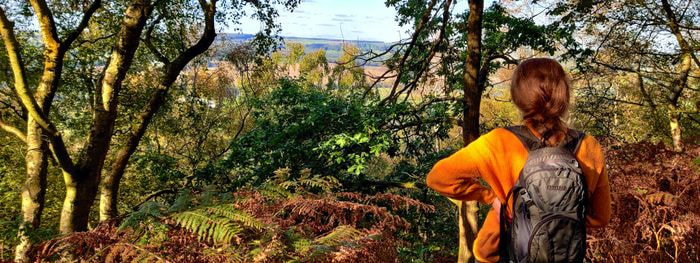 Lady in mustard jumper looking over Otley Chevin from woody hill