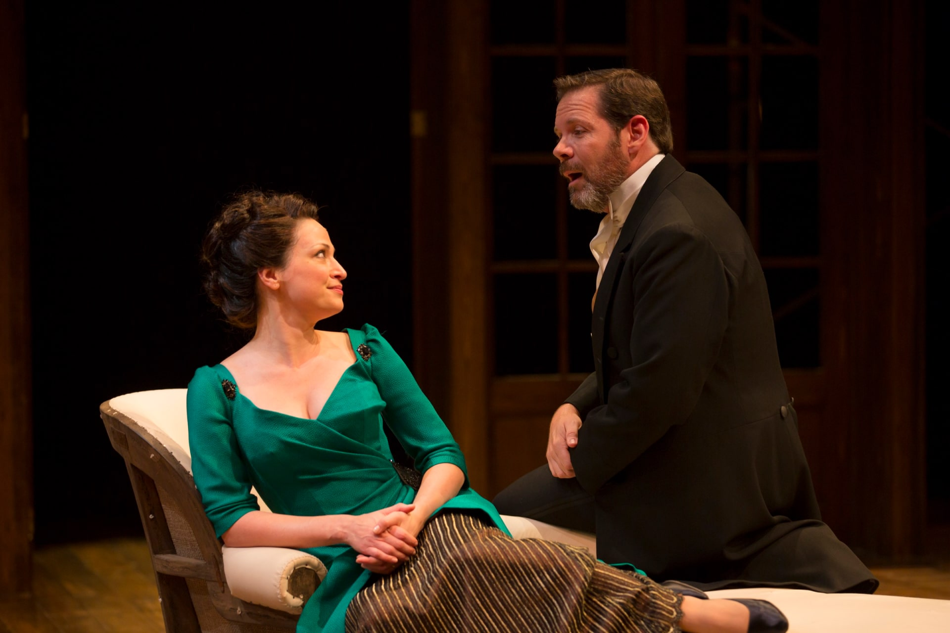 Woman in green dress sits on chaise talking with suited man perched beside.