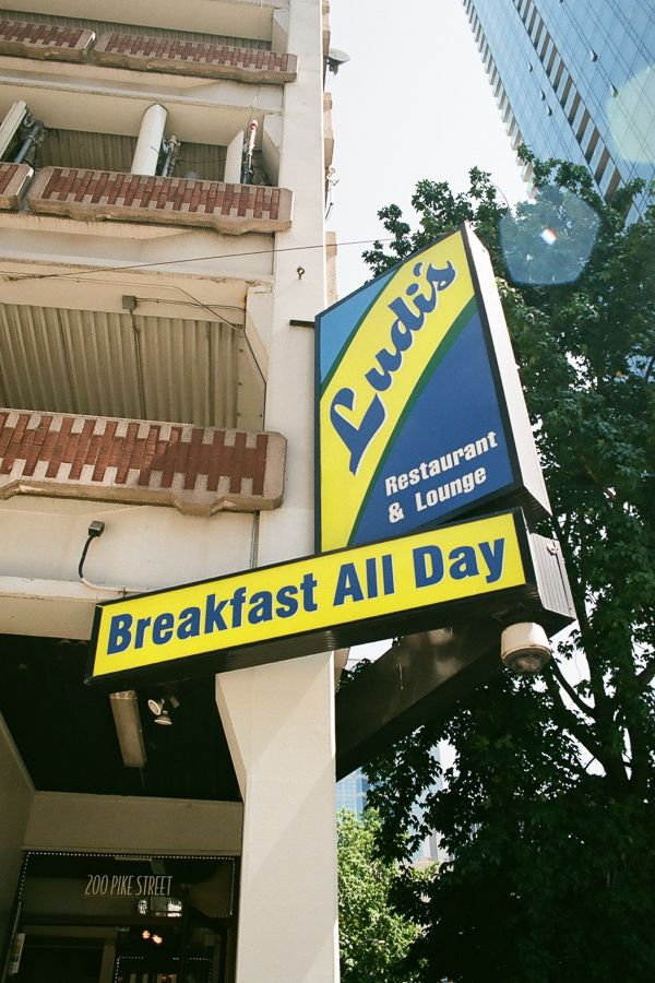 Blue and yellow sign that says Ludi's Restaurant and Lounge and Breakfast All Day.