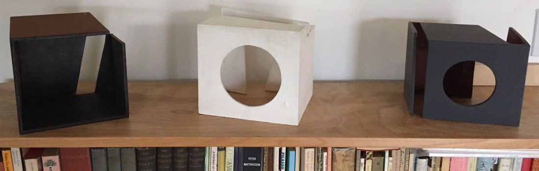 three cubes with holes in one side on a shelf