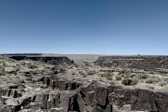 Looking out across a field of broken basalt mesas, and the desert grassland beyond.
