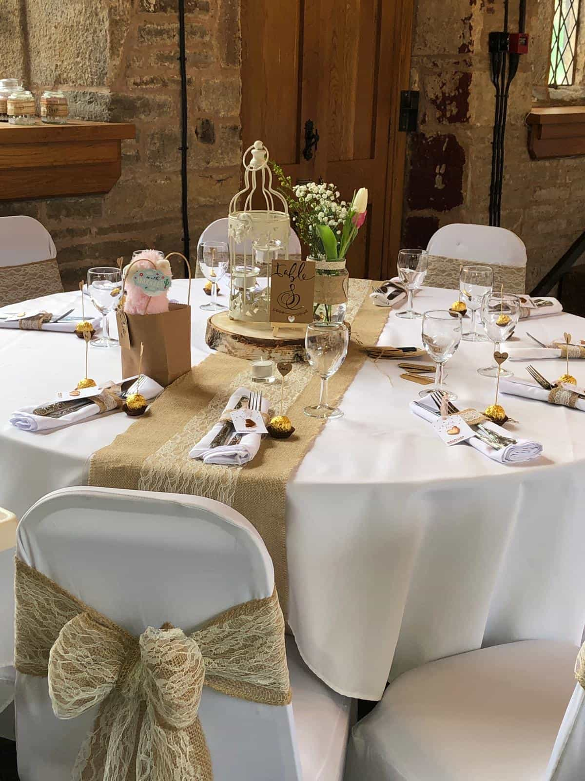 Wedding breakfast table set with hessian sashes and rustic decor