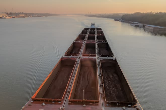 The view directly down towards an empty coal barge traveling west along the Ohio River at dawn.