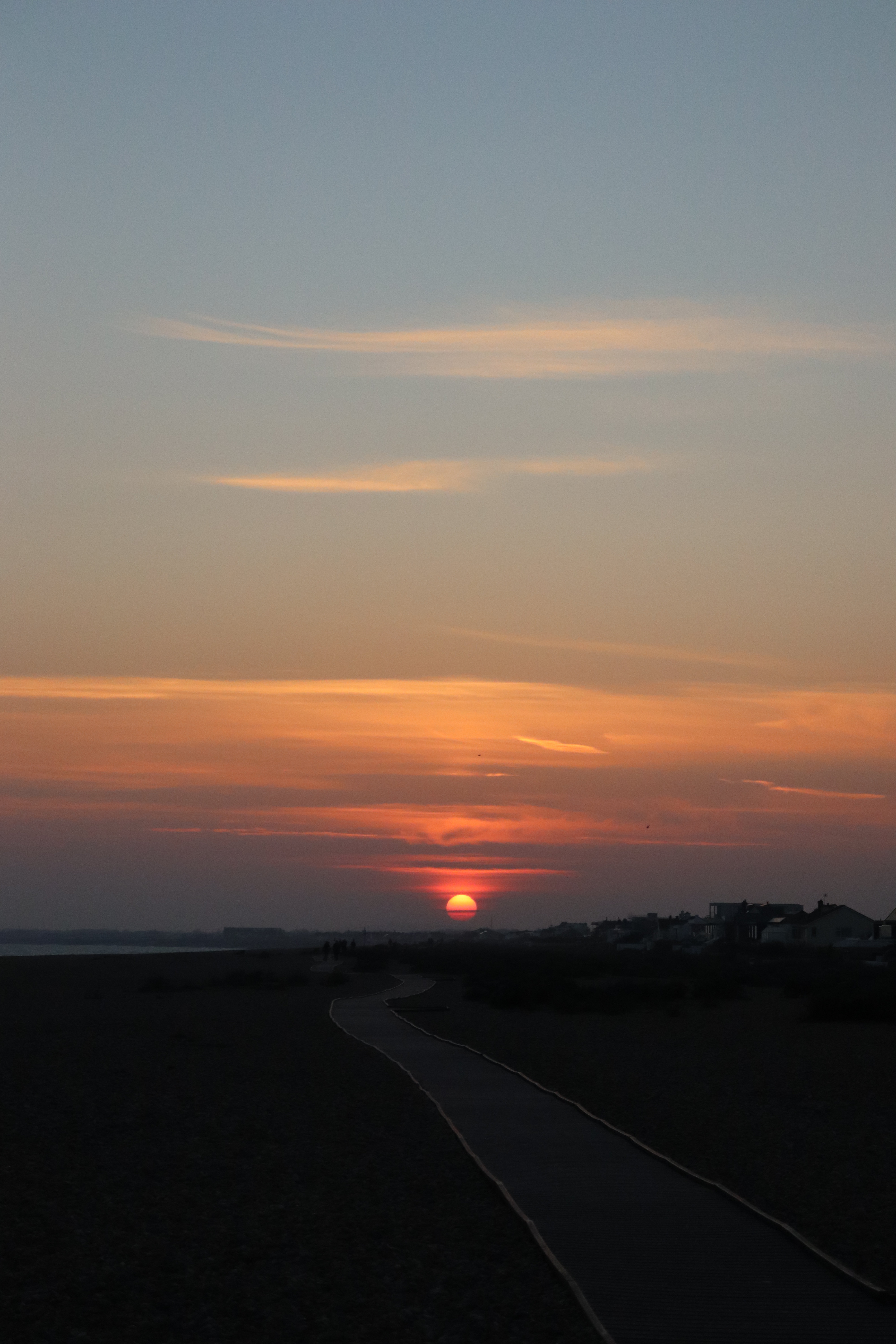 Red sunset reflecting off the clouds over Shoreham beach's boardwalk.