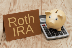 A piggy bank, calculator and a Roth IRA sign sitting on the table