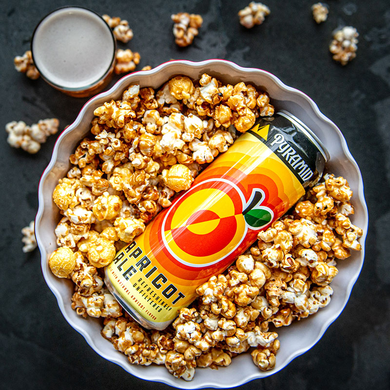 An Apricot Ale can on top of a bowl of caramel corn