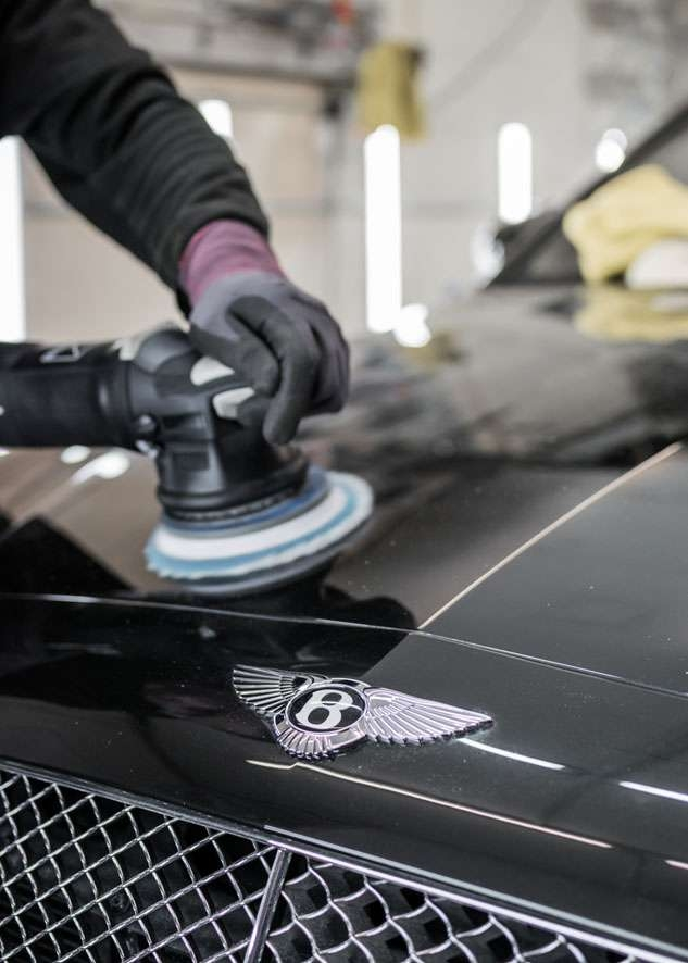 Bentley Flying Spur car being professionally polished using best equipment in glove