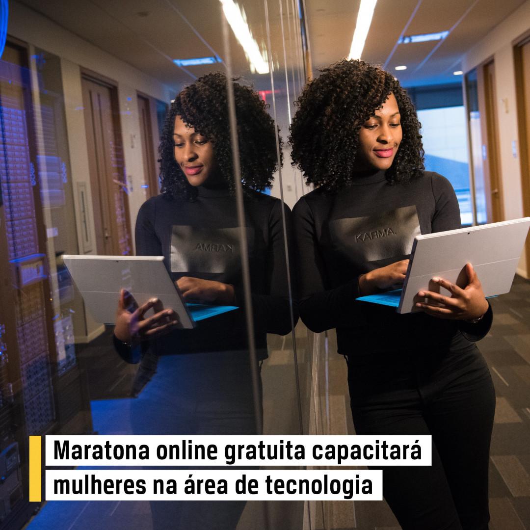 Mulher escostada em uma parede de vidro com computador na mão e o letreiro informativo de Maratona online gratuita capacitará mulheres na área de tecnologia