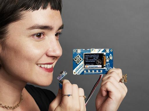 Smiling woman holding up TensorFlowLite microcontroller computer chip. Photo credit: Adafruit