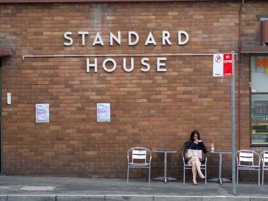 A girl sits in front of Standard House