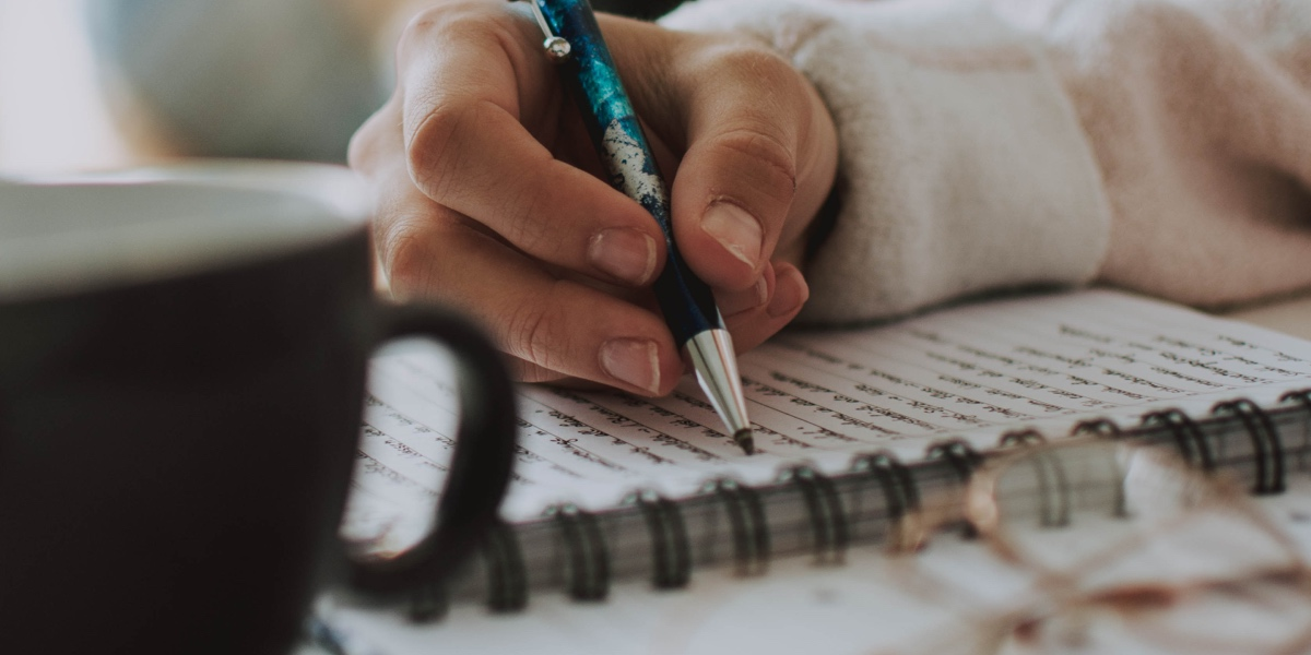 Close up of coffee cup and a writer's hand, holding a pen and writing in a notebook