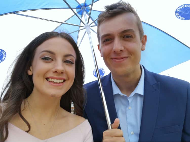 Myself (dressed in a blue suit) and Naomi (in a pink dress) for her graduation, with a large umbrella covering us as we try to stay dry in the rain.