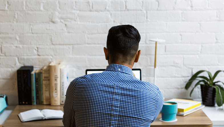 Businessman, business owner, staff member works on laptop at wooden desk with books, plants, coffee cup, notepads to consider if business needs VCFO #business
