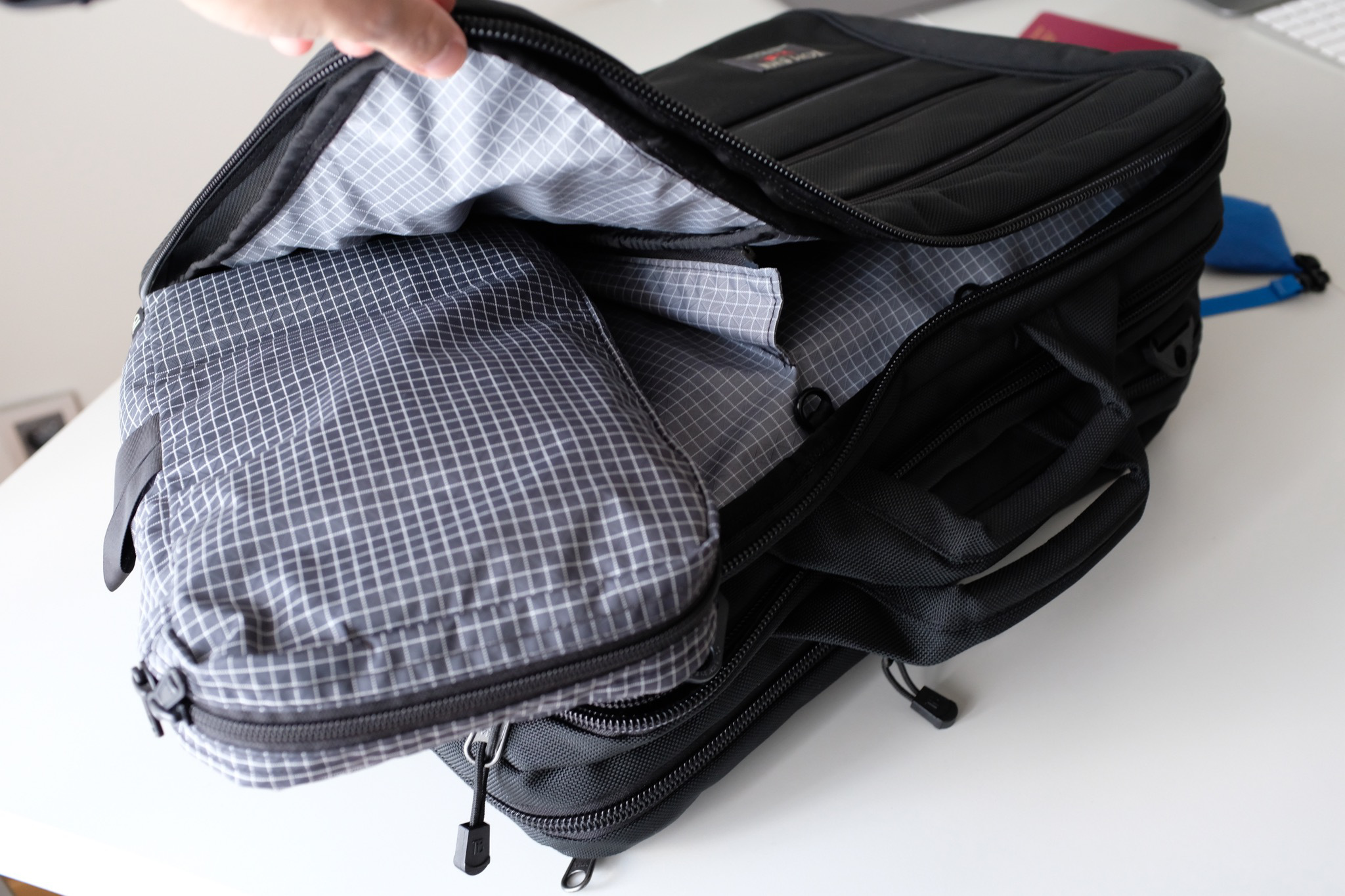 The front compartment has a divider which you can use to separate your clothing. There are also custom fitted packing cubes for each divided section.