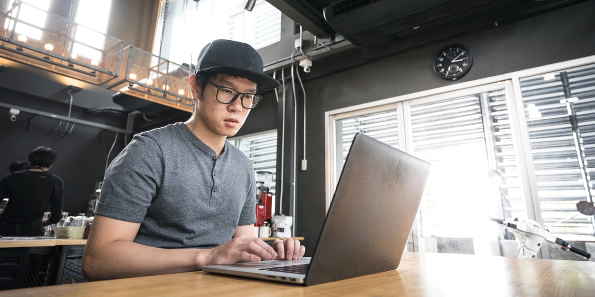 A UX bootcamp graduate sitting in front of a laptop, working on his portfolio