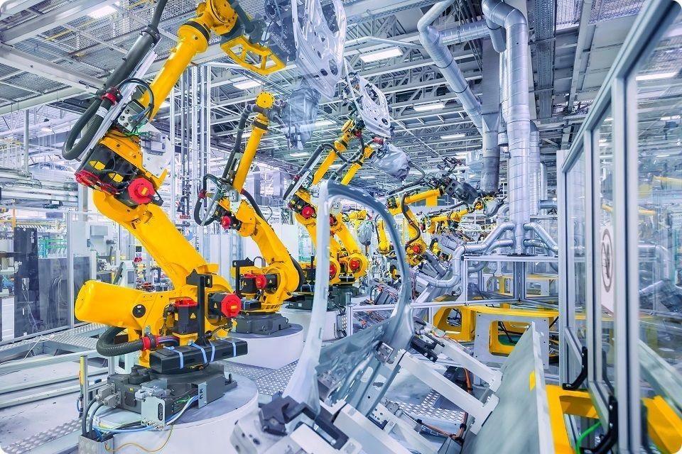 Industrie du futur 4.0 - Une rangée alignée de plusieurs robots orange dans une industrie de grande production (production automobile peut-être ?)