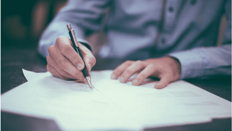 Man in blue shirt writes with pen on paper whilst avoiding 5 cashflow at all costs from a list by Futrli for accountants and business owners and bookkeepers #cashflow