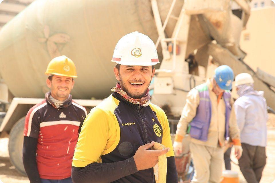 Qualité de Vie au travail - Un ouvrier en gros plan souriant avec un casque blanc sur un chantier. En arrière plan un autre ouvrier souriant avec un casque jaune, un autre ouvrier avec un casque bleu regarde au sol et un dernier avec un casque blanc vu de dos. On devine un camion toupie en fond d'écran.