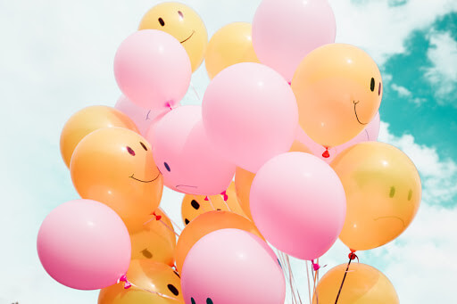 Pink and yellow balloons with smiley faces.