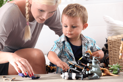 A nanny and a child playing with toys