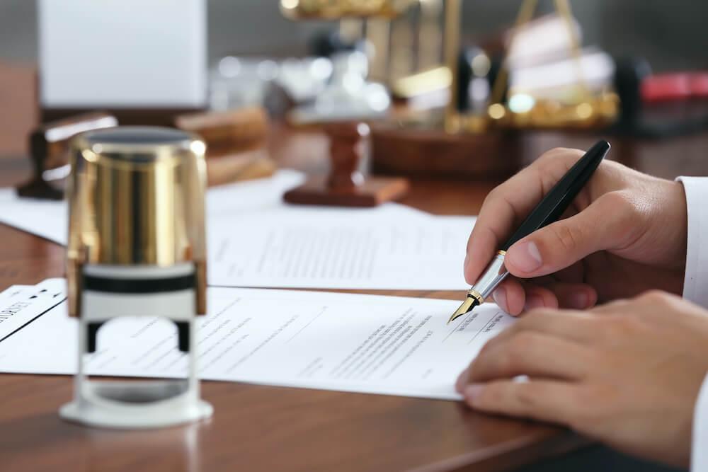 Hände unterschreiben Testament auf Holztisch