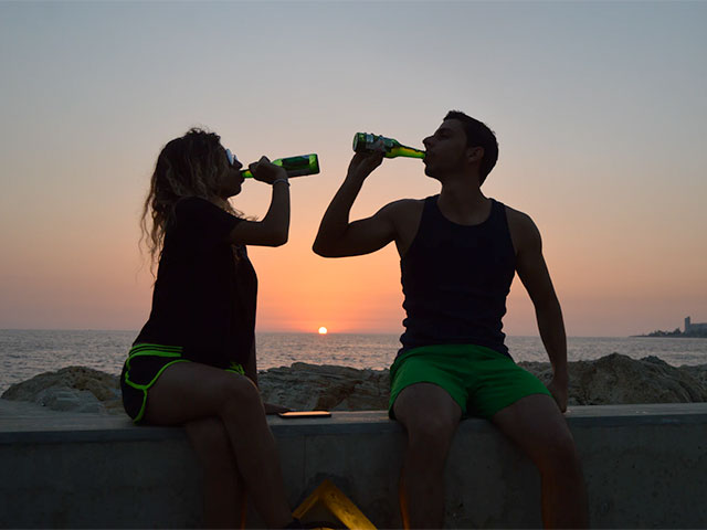 People chugging a bottle of beer at sunset near the beach