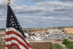 An American flag in front of a natural disaster