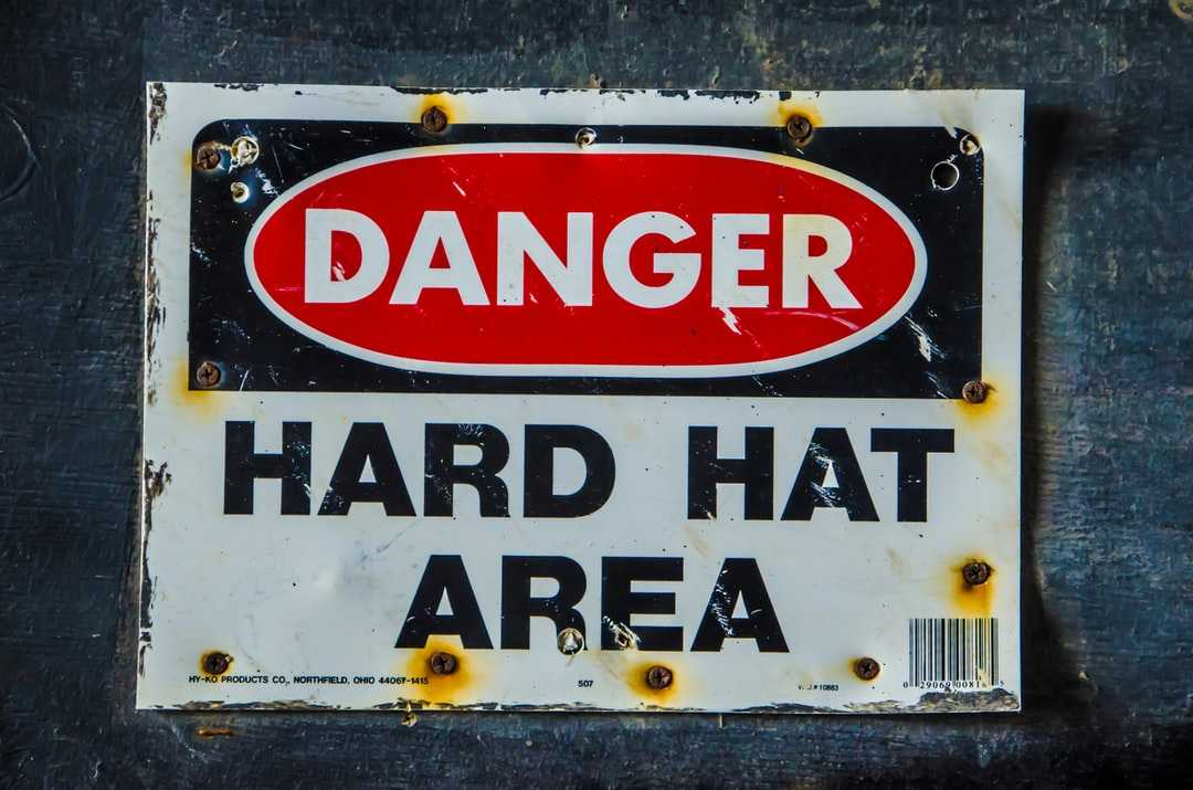 Old industrial warning sign that reads, Warning Hard hat area